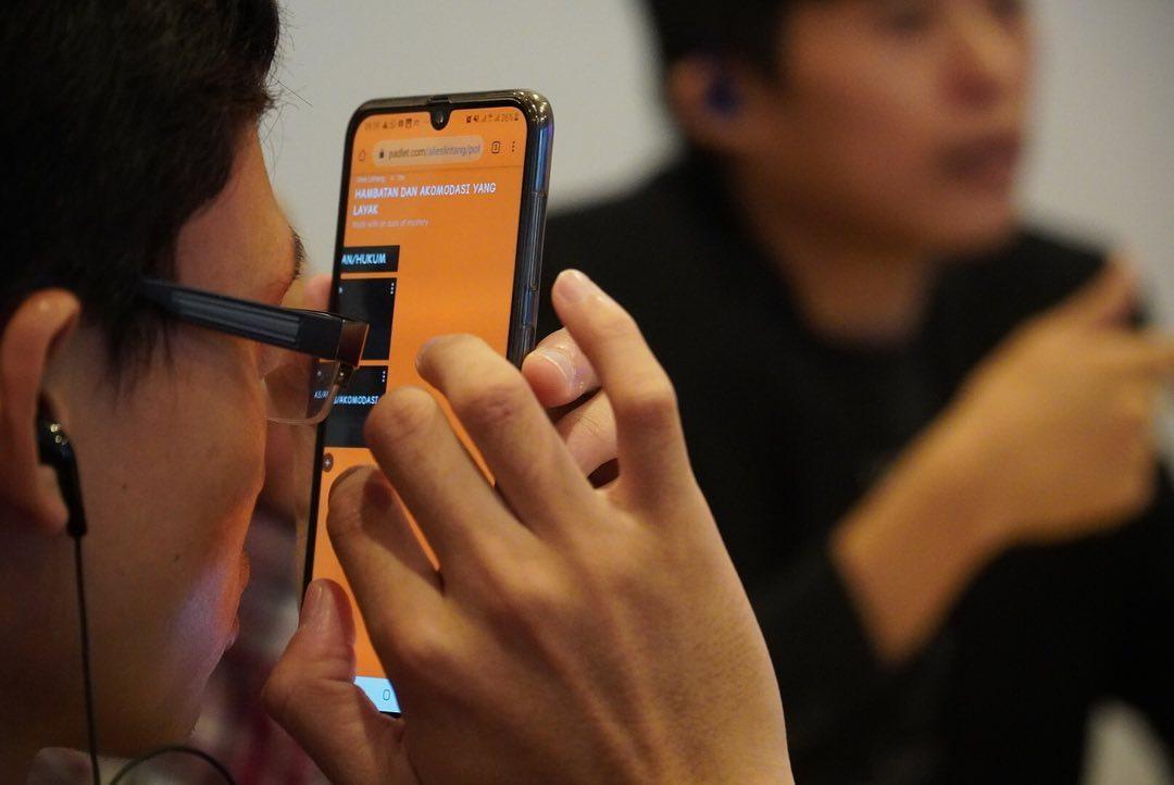 Seorang lelaki low vision mengoperasikan smartphonenya.