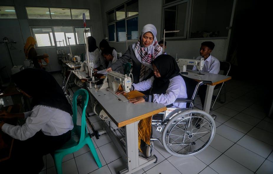 Beberapa orang dalam ruangan pelatihan menjahit, seseorang di atas kursi roda sedang praktik pelatihan.